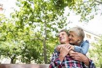 Heureux mignon couple aîné câlin sur banc au parc — Photo de stock