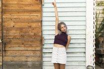 Портрет молодой женщины с окрашенными волосами, стоящей с поднятой рукой перед деревянной стеной — стоковое фото