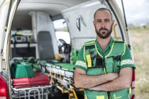 Paramedic standing with arms crossed in front of ambulance — Stock Photo
