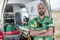 Paramédico em pé com os braços cruzados na frente da ambulância — Fotografia de Stock