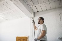 Smiling man painting ceiling of a garage — Stock Photo