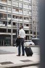 Homme d'affaires avec la valise dans la ville — Photo de stock