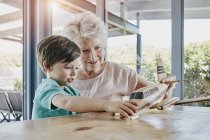 Grandson and grandmother playing with toy airplane — Stock Photo