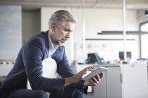 Зрелый бизнесмен, использующий планшет в офисе — стоковое фото