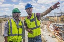 Строитель разговаривает с человеком на стройке, указывая где-то — стоковое фото