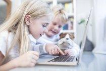 Брат і сестра з приємні іграшки, використовуючи ноутбук разом — стокове фото