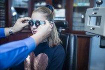 Девушка делает тест на зрение у оптометриста — стоковое фото