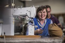 Portrait of smiling seamstress in shoemaker's workshop — Stock Photo
