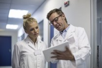 Man and woman in lab coats looking at tablet together in clinic — Stock Photo