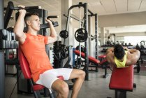 Two sporty men exercising in gym — Stock Photo