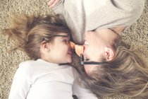 Mother and daughter lying on the carpet wearing funny glasses with plastic nose — Stock Photo