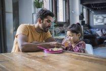 Отец кормит дочь сидя за кухонным столом — стоковое фото