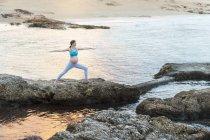 Беременная женщина, практикующая йогу на скалистом побережье моря — стоковое фото