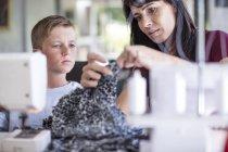 Мать учит сына с материалом на швейные машины — стоковое фото