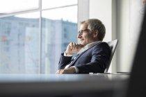 Homme d'affaires, regardant par la fenêtre — Photo de stock