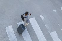 Businessman with baggage crossing street while using cell phone — Stock Photo