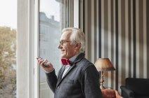 Homme âgé utilisant un téléphone portable à la fenêtre — Photo de stock