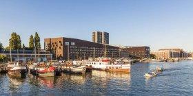 Niederlande, amsterdam, knsm insel mit piraeus wohnhaus und hausbooten im vordergrund — Stockfoto