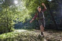 Турист, балансуючи на стовбур дерева в лісі — стокове фото