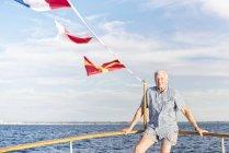 Homem idoso confiante de pé no barco e olhando para a câmera — Fotografia de Stock