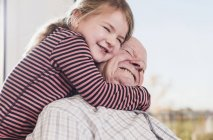 Close-up of Granddaughter embracing grandfather in front of window — Stock Photo