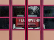 Fire engine behind closed doors of fire station — Stock Photo