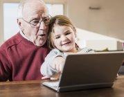 Nonno e nipote mezzo computer portatile insieme — Foto stock