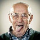 Портрет старшого людини, потягнувши обличчя і, дивлячись на камеру — стокове фото