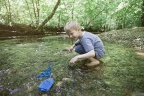 Boy playing with a toy boat in a forest brook — Stock Photo
