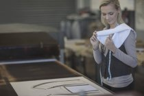 Young woman working on template in tailor shop — Stock Photo
