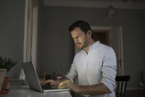 Concentrated businessman using laptop at home — Stock Photo