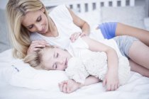 Mother looking at sleeping daughter in bed — Stock Photo