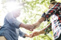 Low angle of happy cute senior couple holding hands at park — Stock Photo