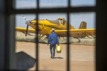 Mechanic carrying jerry cans towards yellow crop dusting plane — Stock Photo
