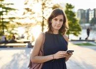 Alemania, mujer joven con teléfono inteligente explorar Hamburgo - foto de stock