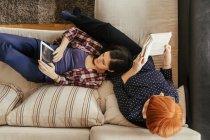 Madre e figlia adulta sul divano con tablet digitale e libro, vista aerea — Foto stock