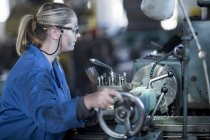 Caucasian woman operating machine in workshop — Stock Photo