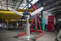 Männliche Mechaniker drängen Flugzeug Propeller im hangar — Stockfoto