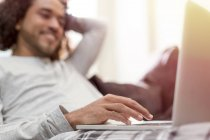 Relaxed man using laptop at home — Stock Photo
