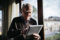 Hombre mayor usando la tableta en casa relajado, cerca de la ventana . - foto de stock