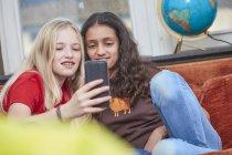 Дві дівчинки на дивані, обмін смартфон — стокове фото