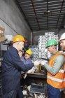 Работники завода по переработке компьютеров смотрят на жесткий диск — стоковое фото