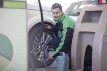 Asistente masculino de ciudad del cabo, Sudáfrica, llenado de neumáticos de coche con el aire en estación de combustible - foto de stock