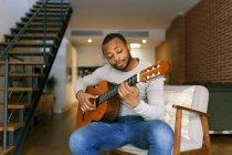 Jeune homme jouant de la guitare à la maison — Photo de stock
