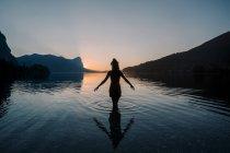 Silhouette de jeune femme debout dans l'eau de lac peu profond au coucher du soleil — Photo de stock