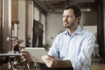 Thoughtful Businessman using tablet in office — Stock Photo