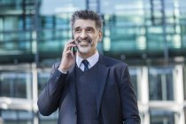 Empresário sorrindo andando ao ar livre com telefone celular — Fotografia de Stock