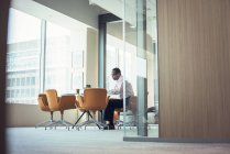 Businessman working alone in empty modern office — Stock Photo