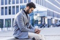 Молодой человек сидит на скамейке и с помощью мини-планшета перед зданием офиса — стоковое фото