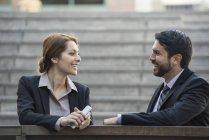 Улыбающаяся деловая женщина и бизнесмен разговаривают на открытом воздухе — стоковое фото